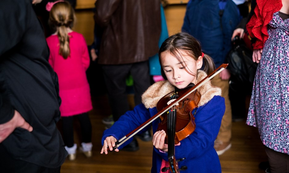 Young girl in blue coat playing a violin