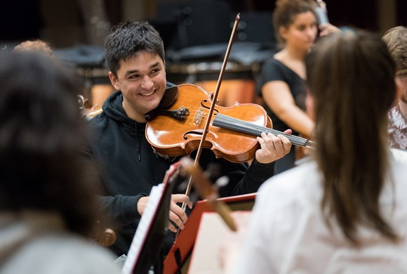 smiling member of youth orchestra playing violin